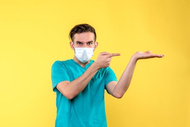 Widok z przodu lekarza płci męskiej na żółtej ścianie