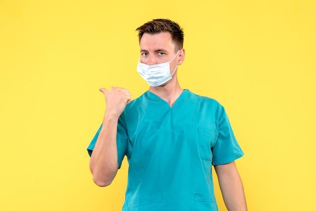 Widok Z Przodu Lekarza Płci Męskiej Noszącej Maskę Na żółtej ścianie Darmowe Zdjęcia