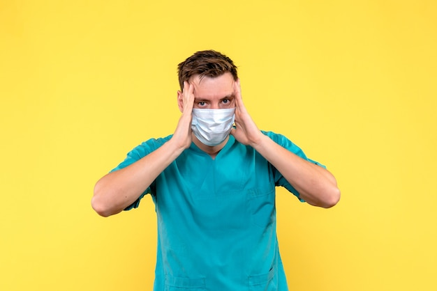 Widok z przodu lekarza płci męskiej o bólu głowy na żółtej ścianie