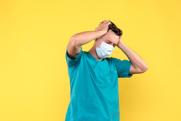 Widok z przodu lekarza płci męskiej o silnym bólu głowy na żółtej ścianie