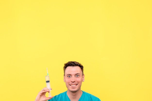 Widok z przodu lekarza płci męskiej posiadającego duży zastrzyk na żółtej ścianie