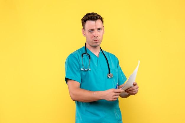 Widok z przodu lekarza płci męskiej posiadających dokumenty na żółtej ścianie