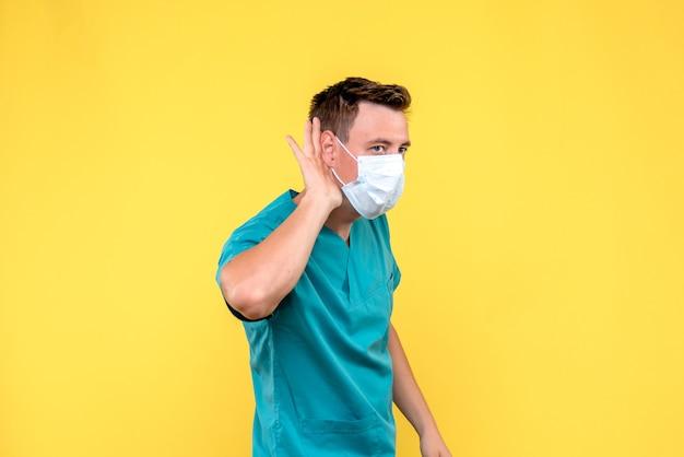 Widok z przodu lekarza płci męskiej słuchania bardziej blisko na żółtej ścianie