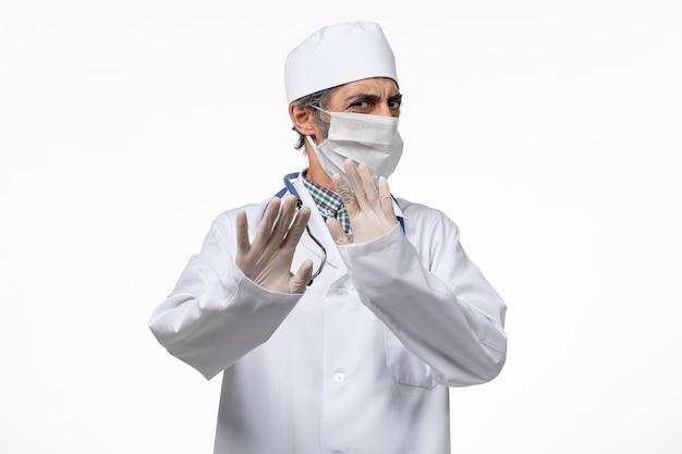 Widok z przodu lekarza płci męskiej w białym kombinezonie medycznym w masce z powodu covid- utrzymywanie dystansu społecznego na białej powierzchni