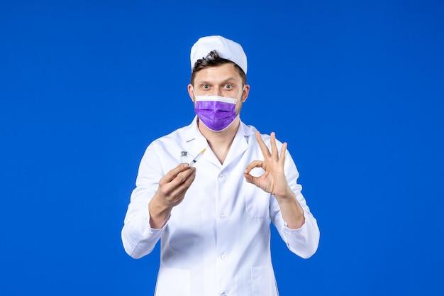 Widok z przodu lekarza płci męskiej w garniturze i masce z zastrzykiem i szczepionką na niebiesko