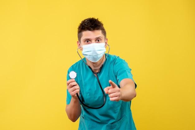Widok z przodu lekarza płci męskiej w garniturze i masce ze stetoskopem na żółtej ścianie