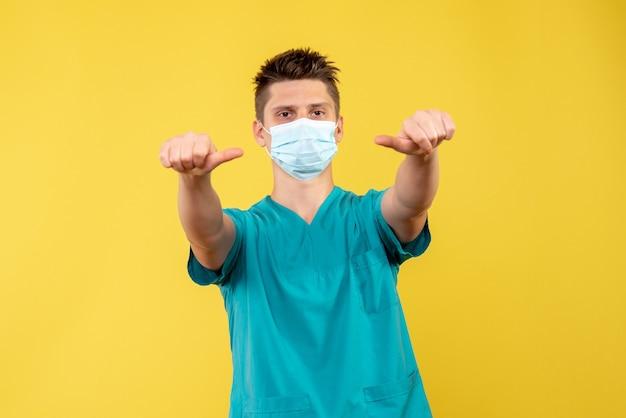 Widok z przodu lekarza płci męskiej w kombinezonie medycznym i sterylnej masce na żółtej ścianie