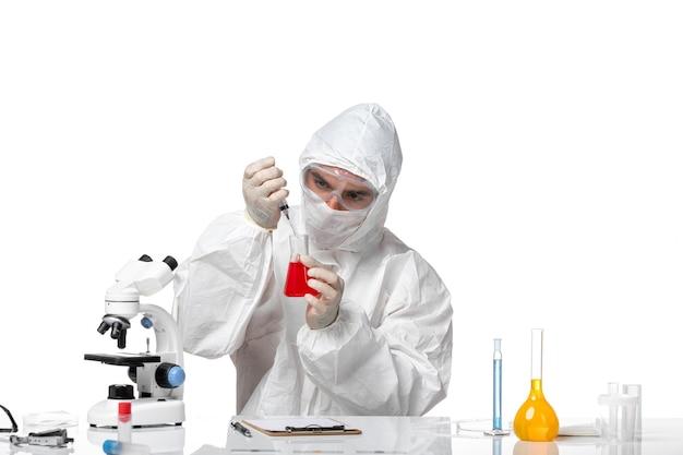 Widok z przodu lekarza płci męskiej w kombinezonie ochronnym z maską z powodu covid pracującego na białej przestrzeni