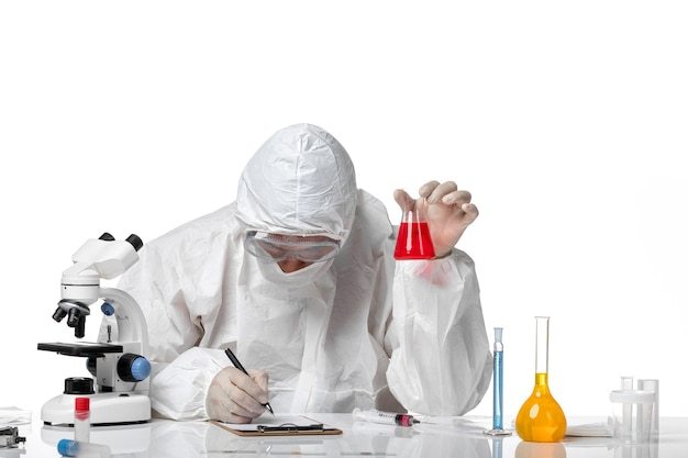 Widok z przodu lekarza płci męskiej w kombinezonie ochronnym z maską z powodu covid trzymającej kolbę z czerwonym roztworem na białej przestrzeni