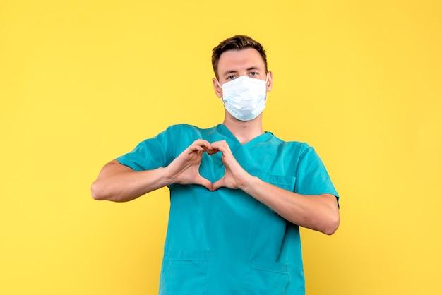 Widok z przodu lekarza płci męskiej wysyłającej miłość na żółtej ścianie