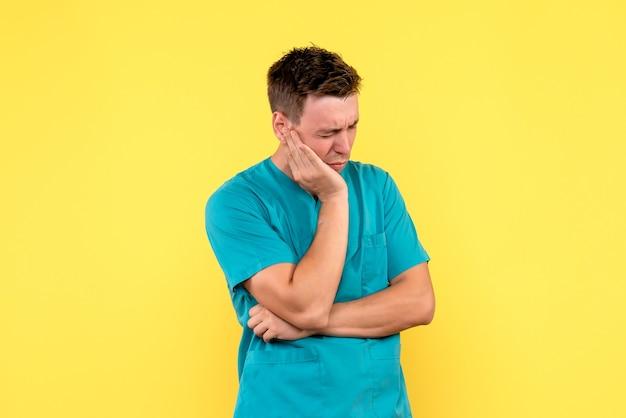 Widok z przodu lekarza płci męskiej z wyrażeniem podkreślił na żółtej ścianie