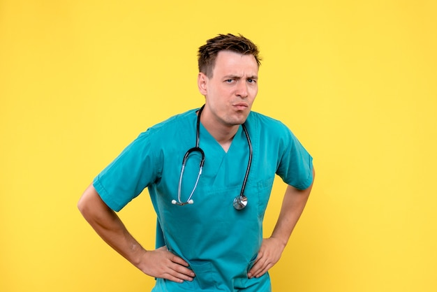 Widok z przodu lekarza płci męskiej z zmieszanym wyrazem twarzy na żółtej ścianie