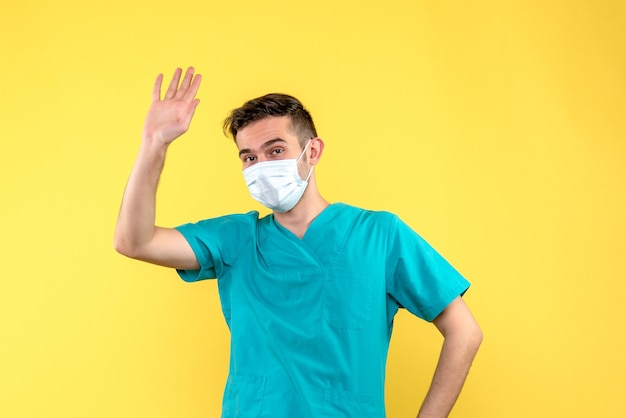 Widok z przodu lekarza płci męskiej ze sterylną maską na żółtej ścianie
