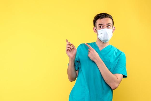 Widok z przodu lekarza w masce na żółtej ścianie