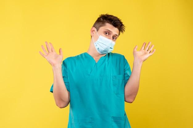 Widok z przodu lekarza w masce ochronnej na żółtej ścianie