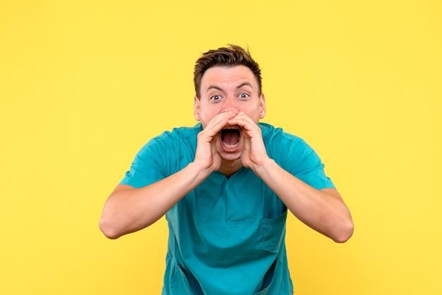 Widok z przodu lekarza wzywającego głośno na żółtej ścianie