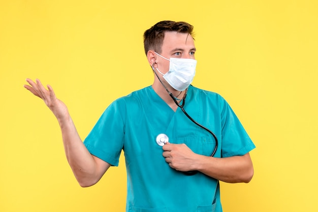 Widok z przodu lekarza z maską i tonometrem na żółtej ścianie