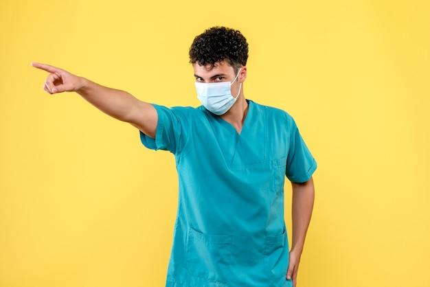 Widok z przodu lekarza zły lekarz w masce wskazuje na bok