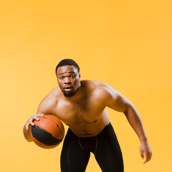 Widok z przodu lekkoatletycznego mężczyzna gra w koszykówkę półnagi