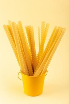 Widok z przodu makaron wewnątrz kosza długo uformowany surowy wewnątrz żółty kosz na kremowym tle posiłek żywności włoskiego spaghetti