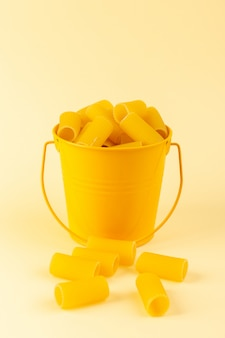 Widok z przodu makaron wewnątrz kosza uformowany surowy wewnątrz żółty kosz na kremowym tle posiłek żywności włoskiego spaghetti