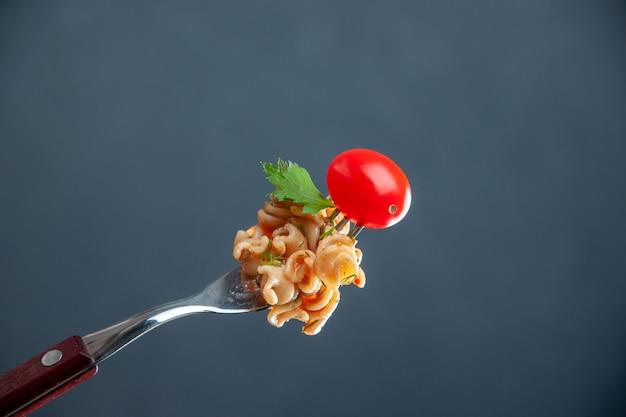 Widok z przodu makaronu rotini z pomidorami cherry na widelcu na szarej odizolowanej powierzchni kopii przestrzeni