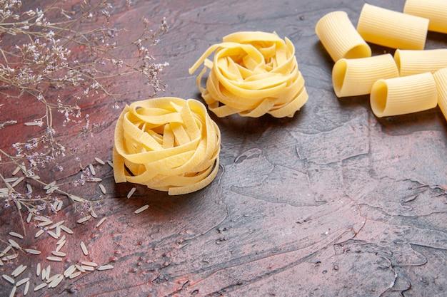 Widok z przodu makaronu surowego na ciemnej powierzchni makaronu w kolorze ciasta