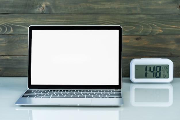 Widok z przodu makiety laptopa i budzik z drewnianym tłem na stole roboczym