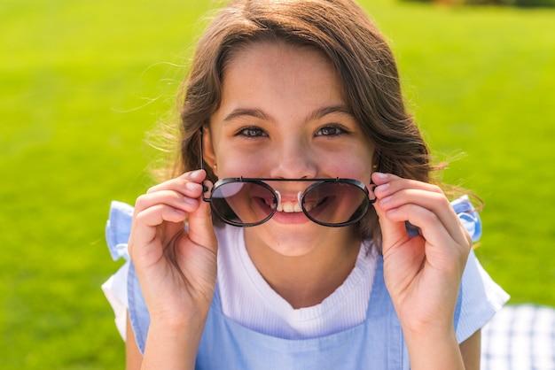 Widok z przodu mała dziewczynka nosi fajne okulary przeciwsłoneczne
