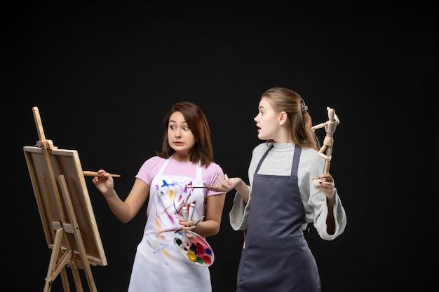 Widok z przodu malarki rysujące ludzką postać na sztalugach na czarnej ścianie zdjęcie kolor rysować obrazy praca sztuka obraz artysty