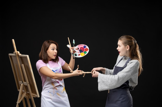 Widok z przodu malarki rysujące obraz postaci ludzkiej na sztalugach na czarnej ścianie rysować obrazy artysta kolor praca zdjęcie zdjęcie