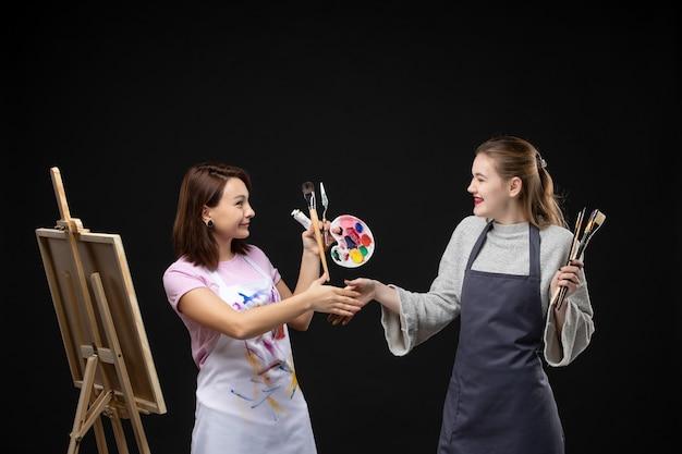 Widok z przodu malarki trzymające farby i frędzle do rysowania na czarnej ścianie obraz pracy kolory sztuki artysta zdjęcie rysować malarstwo
