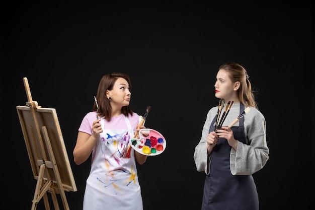 Widok z przodu malarki trzymające farby i frędzle do rysowania na czarnej ścianie obraz sztuka kolor artysta zdjęcie zadanie rysowanie malowanie