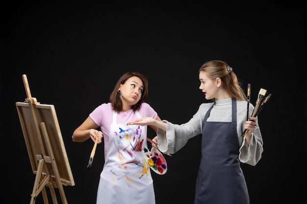 Widok z przodu malarki trzymające farby i frędzle do rysowania na czarnej ścianie rysować obrazy obraz pracy sztuka zdjęcie kolor artysta