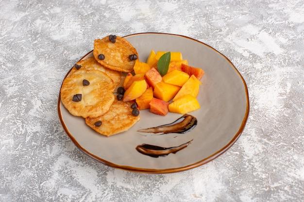 Widok z przodu małe ciasteczka ciasteczka wewnątrz talerza ze świeżymi pokrojonymi brzoskwiniami na lekkim stole, ciasto herbatniki cukier słodkie wypieki