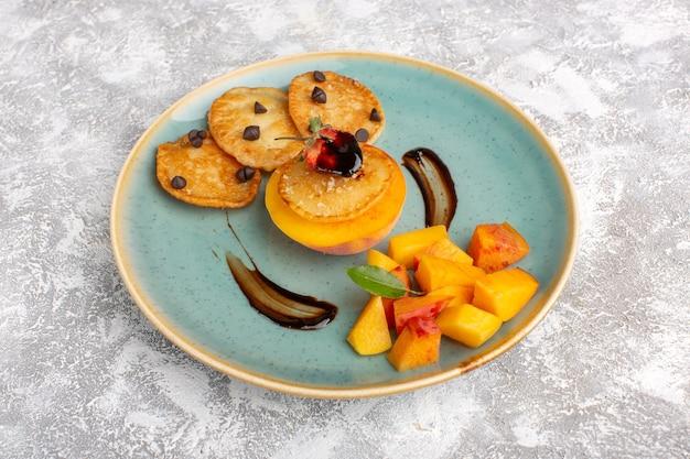 Widok z przodu małe ciasteczka wewnątrz talerza ze świeżymi pokrojonymi brzoskwiniami na lekkim stole, ciasto herbatniki cukier słodkie ciasto owocowe