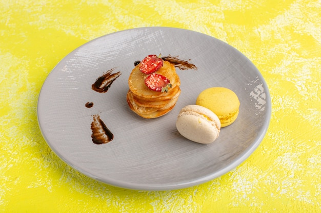 Widok z przodu małe ciastka wewnątrz talerza z makaronikami na żółtym stole, upiec słodkie ciasto owocowe z herbatą