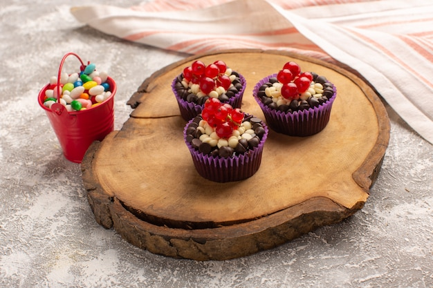 Widok z przodu małe czekoladowe ciasteczka z żurawiną i cukierkami na szaro