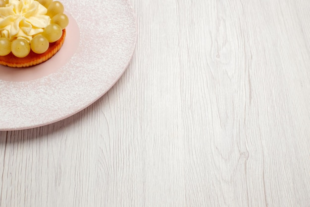Widok z przodu małe kremowe ciasto z winogronami na białej podłodze ciasto owocowe ciastko deserowe ciastko