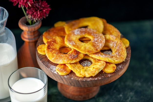 Widok z przodu małe pyszne ciasta w kształcie pierścienia ananasa z mlekiem na ciemnej powierzchni