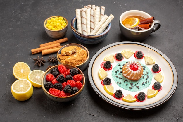 Widok z przodu małe pyszne ciasto z plasterkami cytryny cukierkami i filiżanką herbaty na ciemnym tle ciasto biszkoptowe owoce cytrusowe słodkie ciastko