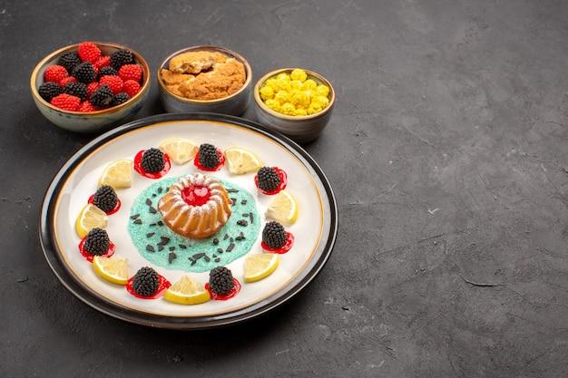 Widok z przodu małe pyszne ciasto z plasterkami cytryny i cukierkami na ciemnym tle biszkoptowe ciasto owocowe słodkie ciastko cytrusowe