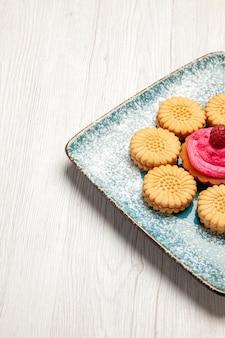 Widok z przodu małe słodkie ciasteczka z ciastem owocowym wewnątrz talerza na białym biurku słodkie ciasteczka biszkoptowe ciasto cukier