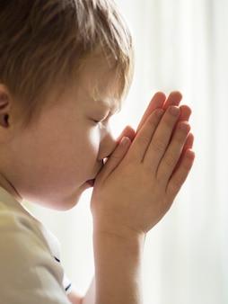 Widok z przodu małego chłopca modlącego się