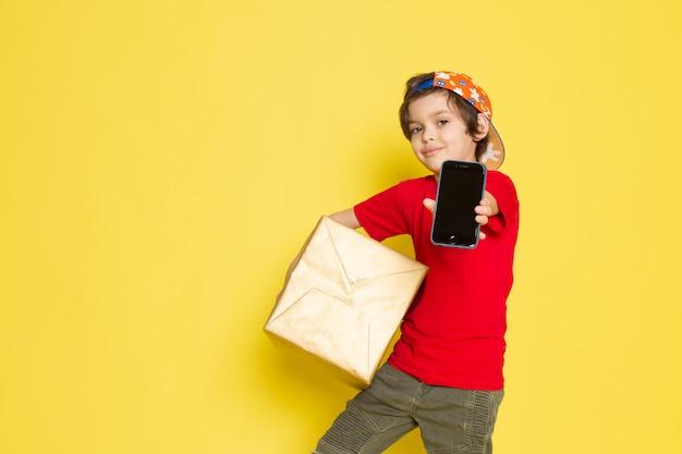 Widok z przodu małego chłopca w czerwonej czapce w kolorowe t-shirty i spodnie w kolorze khaki, trzymającego pudełko na żółtym tle