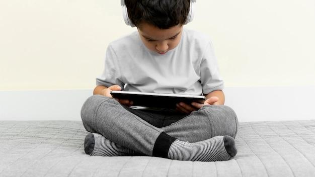 Widok z przodu małego chłopca za pomocą tabletu w łóżku