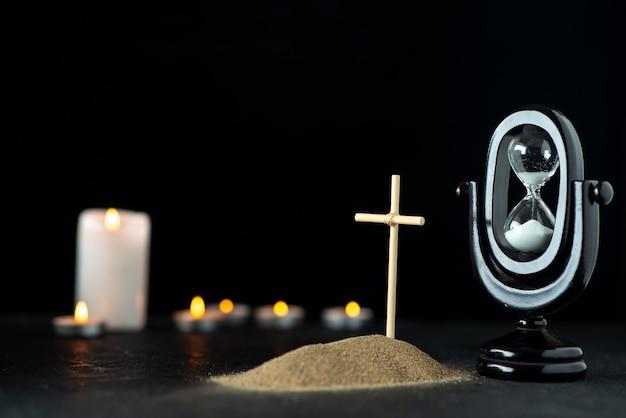 Widok z przodu małego grobu z klepsydrą i świecami w ciemności