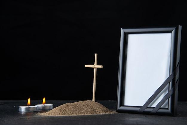 Widok z przodu małego grobu z krzyżem i ramką na obraz w ciemności