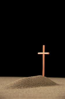 Widok z przodu małego grobu z krzyżem w ciemności