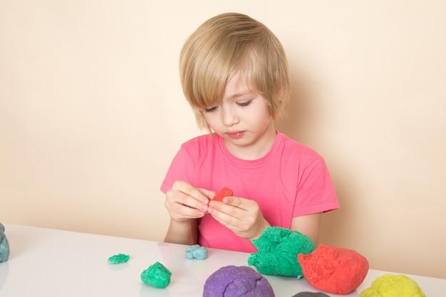 Widok z przodu małego słodkiego chłopca w różowej koszulce bawiącej się kolorowym piaskiem kinetycznym